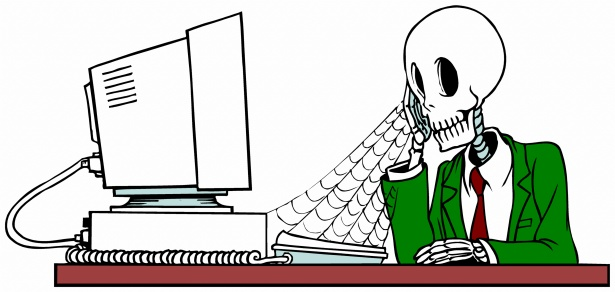 A skeleton sitting in front of a desktop with phone in hand