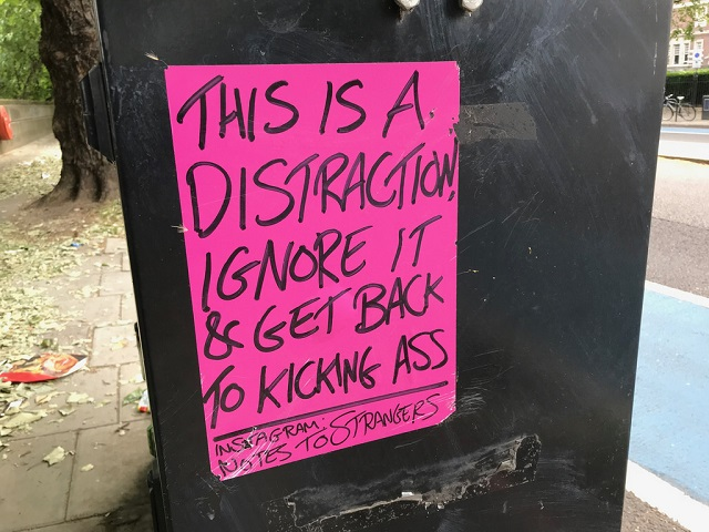 "A sign attached to a tree. It reads ""This is a distraction. Ignore it and get back to kicking Ass"