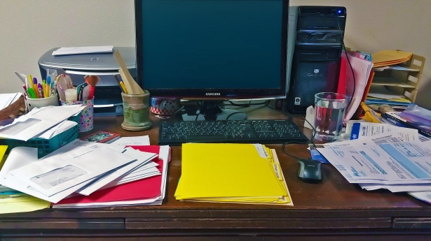 A desk at work with too many papers, files and clutter