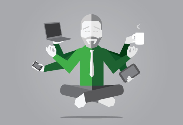 A guy sitting in a yoga pose with a smile and juggling multiple tasks