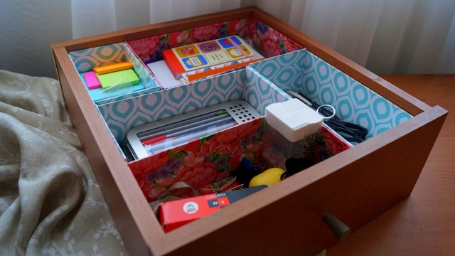 A desk drawer with some office supplies neatly stored in