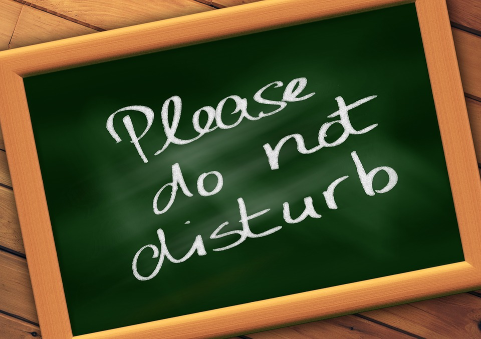 """A green chalkboard with the words """"please do not disturb"""" written on it"""