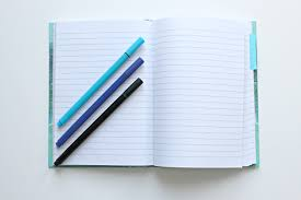 An open notebook. Three different coloured pens are lying on it.
