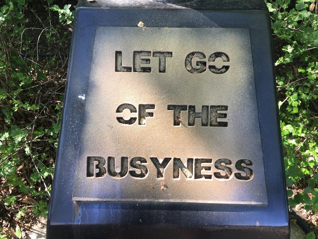 "A gravestone. The words ""Let Go of The Busyness"" are etched into it"