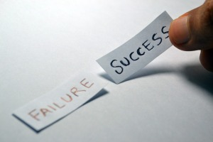 "Two pieces of paper with the words ""failure"" and ""success"" written on them"