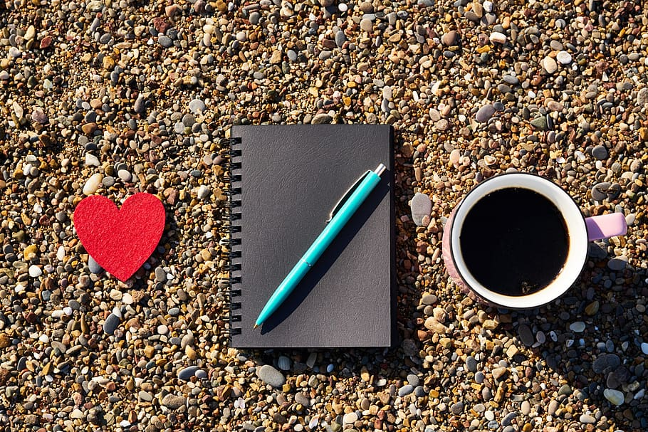 A heart, a book, a pen and a mug of coffee