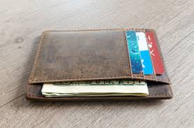 A wallet with some currency and plastic cards in it